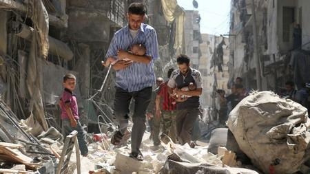 des-syriens-portent-des-bebes-dans-leurs-bras-a-travers-les-ruines-apres-des-raids-aeriens-sur-un-quartier-rebelle-d-alep-le-11-septembre-2016_5667007.jpg